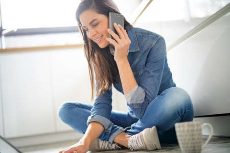 Woman using laptop and smartphone, sitting on floor