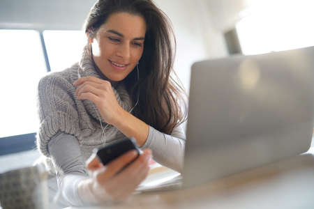 Woman connected with laptop and smartphone, using earphones