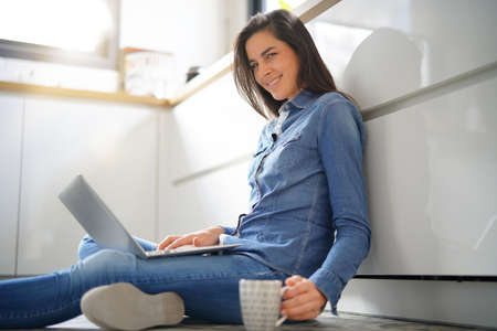 Woman sitting on floor connected with laptop