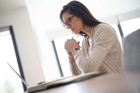 Woman in office working on laptop computer                          Standard-Bild