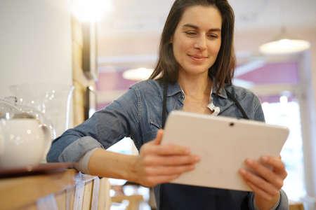 Waitress in coffee shop taking order on digital tablet Standard-Bild