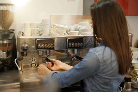 Waitress serving expresso from coffee machine