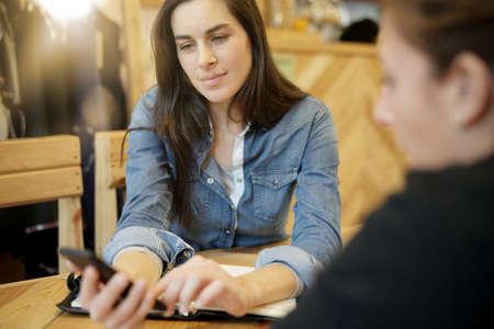 Active woman meeting client at coffee shop Standard-Bild