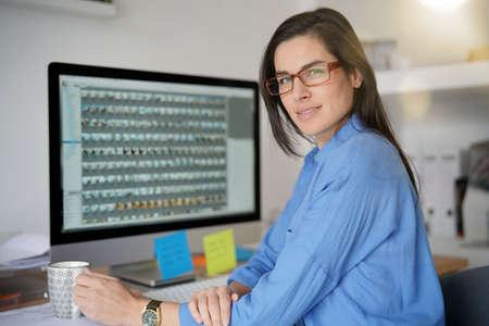 Woman in office working on desktop computer Standard-Bild