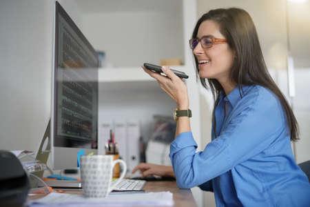 Cheerful woman at work talking on phone in office Standard-Bild