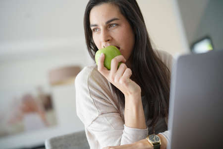 Brunette girl working on laptop, eating green apple Standard-Bild