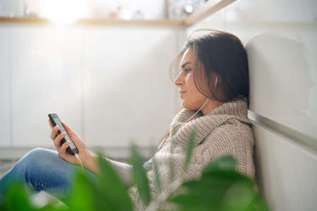 Woman relaxing at home listening to music with smartphone Standard-Bild