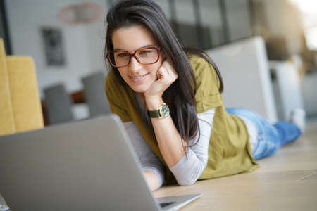 Brunette woman laying on floor, connected on internet with laptop