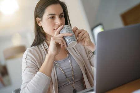 Home-office worker in front of laptop drinking tea Standard-Bild