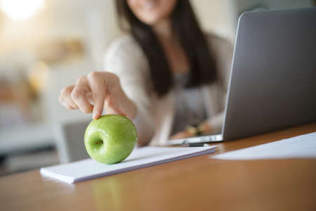 Dark-haired woman at work holding green apple
