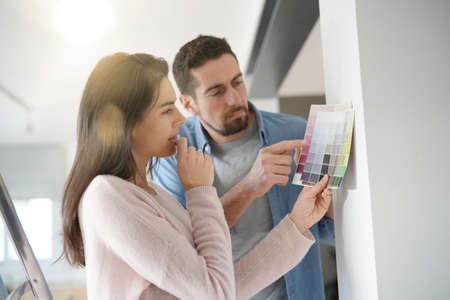 Couple looking at colour sample to renovate home interior Imagens