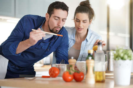 Couple at home having fun cooking together