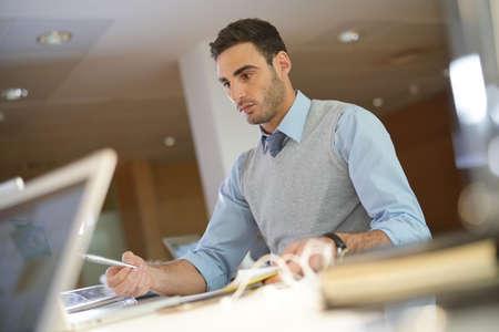Portrait de jeune homme d'affaires travaillant dans le bureau