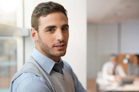 Portrait of young businessman looking at camera
