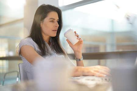 Femme d'affaires au bureau, boire du café