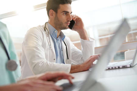 Young doctor in office working on laptop and talking on phone