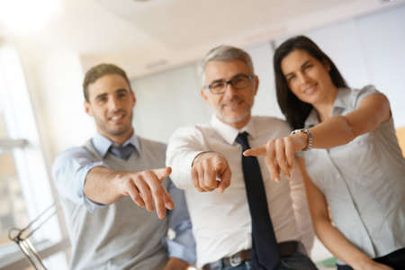Start-up people pointing at camera