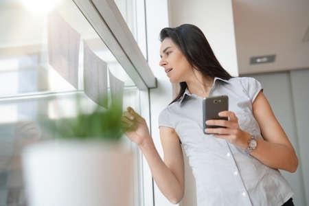 Femme d'affaires au bureau de détente, en utilisant un smartphone