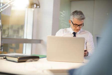Homme d'affaires mature au bureau travaillant sur ordinateur portable Banque d'images