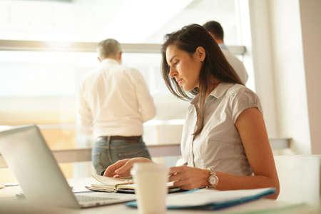 Femme d'affaires au bureau travaillant sur ordinateur portable, équipe en arrière-plan