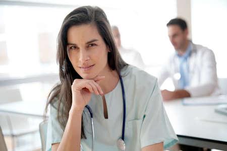 Portrait of nurse, medical team in background