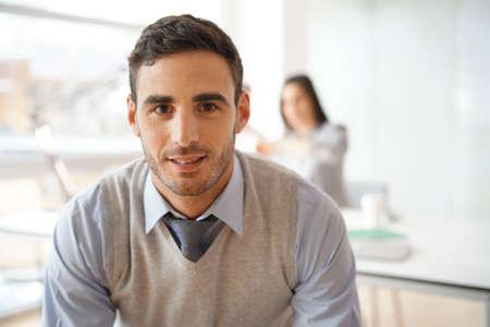Portrait de jeune homme d'affaires en regardant la caméra