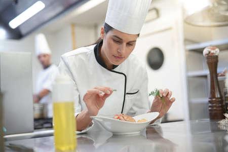 Closeup of cook chef in professional kitchen preparing dish