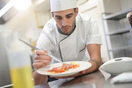 Professional cook garnishing plate in restaurant kitchen