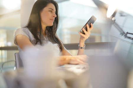 Femme d'affaires au bureau en utilisant un smartphone