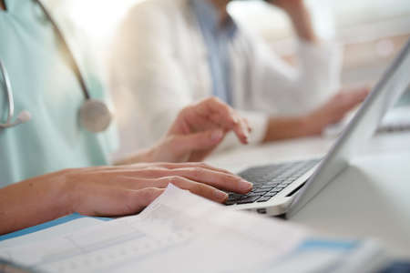 Closeup of nurses hands typing on laptop keyboard Banque d'images