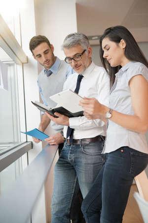 Hommes d'affaires réunis dans le bureau, en regardant les résultats des ventes