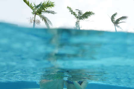 Couple underwater and palms trees on the outside