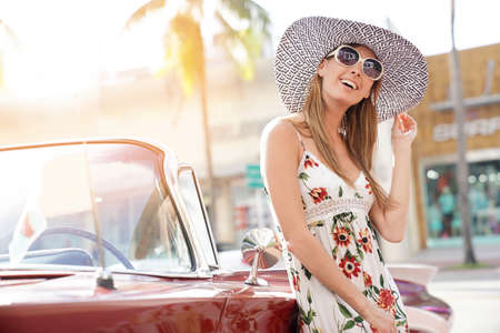 Model posing by old-fashioned car Stock Photo