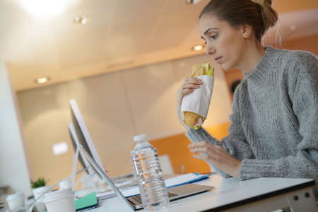 Young woman student eating sandwich in front of laptop computer