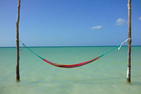 Hammock hanging over crystal clear sea of Caribe