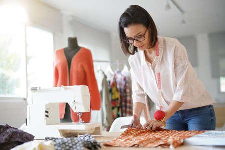 Seamstress woman in atelier preparing pattern