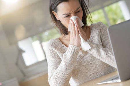 Woman at work having a cold Stock Photo