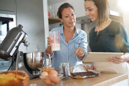 amis fille préparant gâteau ensemble avec un sandwich de pâte Banque d'images