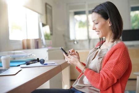 Brunette woman using smartphone in office Stock fotó