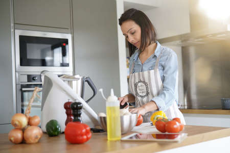 Woman using kitchen robot to prepare dinner