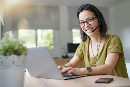 Teleoperator working in office with laptop and headset on