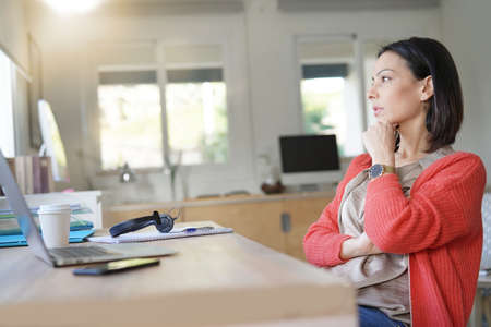 Woman at work looking by window, thoughtful look