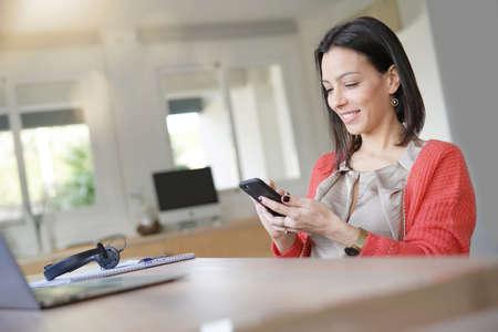 Brunette woman using smartphone in office Standard-Bild