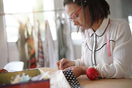 Trendy fashion designer in workshop sewing model
