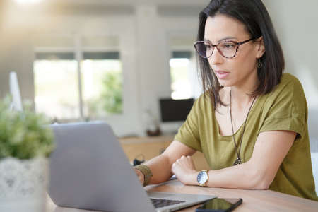 Woman with eyeglasses in office working on laptop