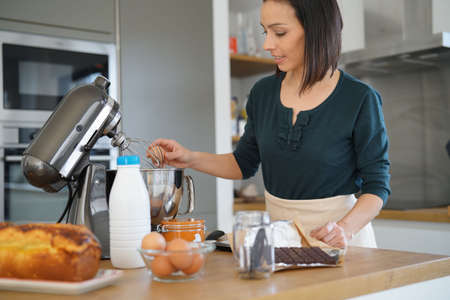 Woman in kitchen preparing cake with pastry robot