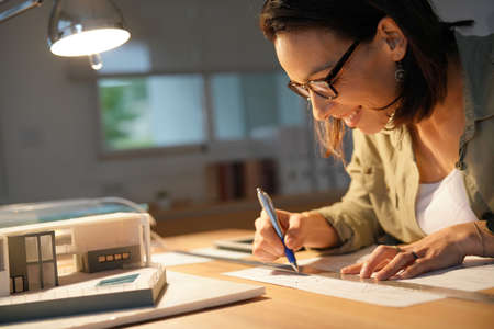 Architect in office drawing on blueprint
