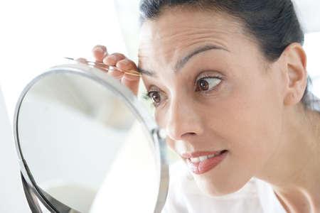 Closeup of woman using tweezers in front of mirror Standard-Bild