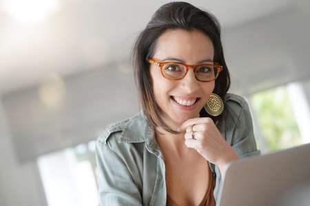 Portrait of smiling brunette girl working on laptop computer