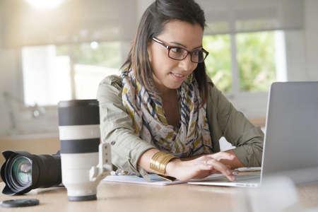 Woman photographer working on laptop computer                            Standard-Bild